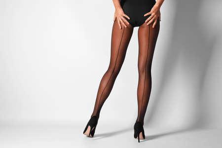 明るい背景に黒いタイツを持つ美しい若い女性の足 写真素材