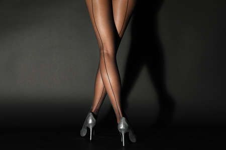 Legs of beautiful young woman in tights on dark background