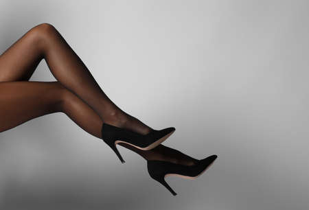 Legs of beautiful young woman in black tights on light background