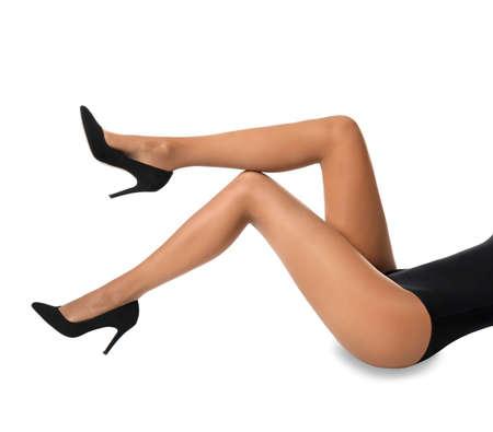 白い背景にタイツを持つ美しい若い女性の足