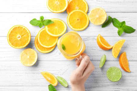 Woman holding mason jar with fresh orange juice on table Reklamní fotografie