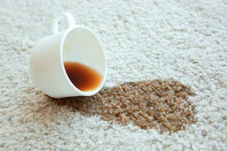 Tasse Kaffee wurde auf weißem Teppich, Abschluss herauf% 00 verschüttet Standard-Bild