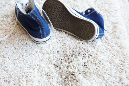 Pair of shoes and dirty footprint on white carpet