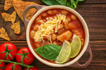 Composition with delicious turkey chili in casserole on wooden table Stok Fotoğraf