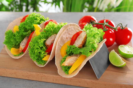 Holder with delicious fish tacos on wooden board