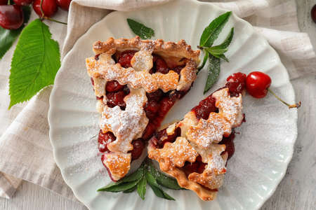 Delicious pieces of cherry pie on white plate