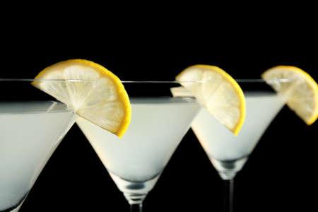 Glasses of lemon drop martini with slices of fruit on black background