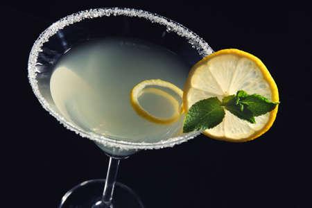 Glass of lemon drop martini with slice of fruit on black background