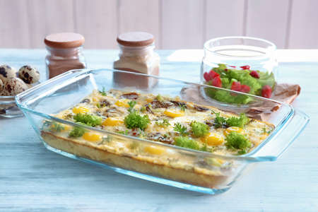 Baking dish with broccoli casserole on wooden table
