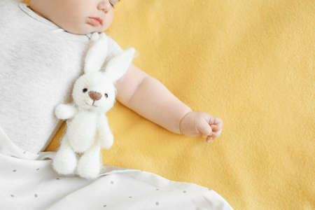 Cute little baby sleeping with toy on bed