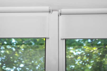Tende a rullo bianche su una finestra di plastica metallica Archivio Fotografico