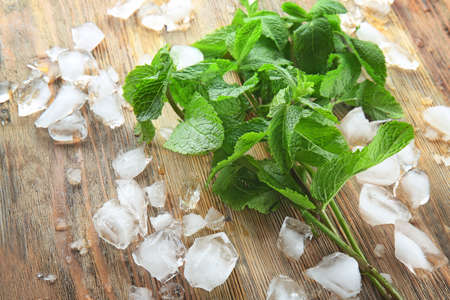 Mint near ice cubes on wooden background Stock Photo