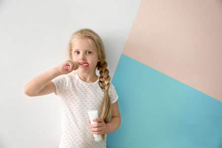 Cute little girl cleaning teeth on color background