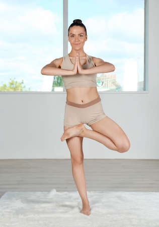 Young beautiful woman doing yoga pose in room with window Stock Photo