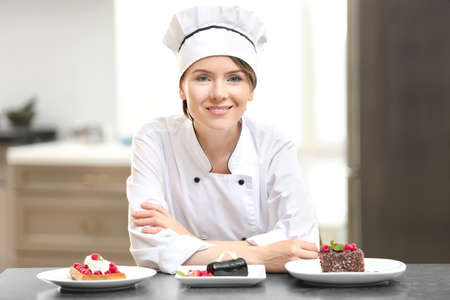 Female chef with tasty desserts in kitchen