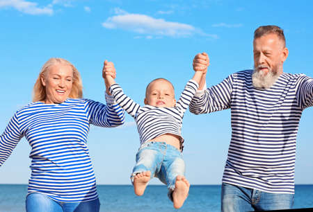 Cute boy with grandparents on sea beach