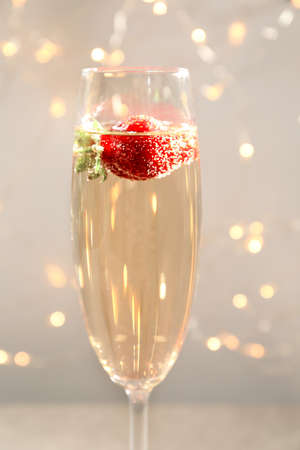 Glass of delicious wine with strawberry against defocused lights