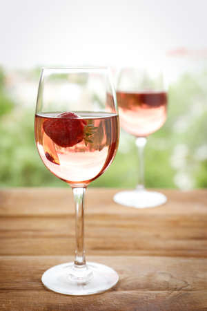 Glass of delicious strawberry wine on blurred background