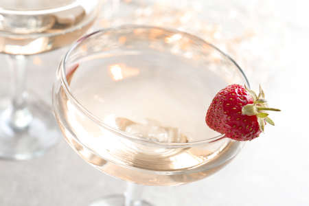 Glass of delicious wine with strawberry on table Stock Photo
