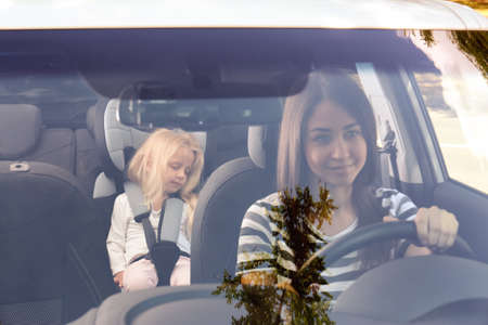 Young woman driving car with small girl in safety seat Stock Photo