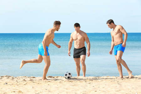 Handsome young men playing football on sea beach