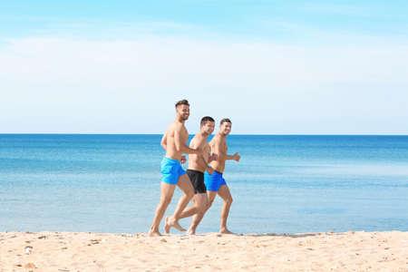 Handsome young men running along sea beach