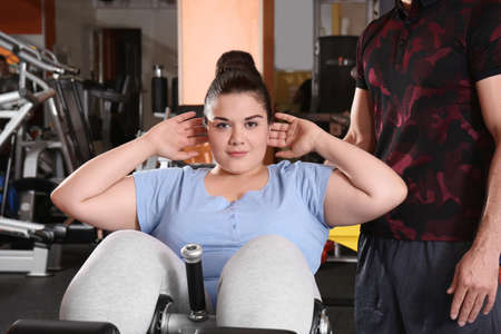 Overweight young woman with trainer in gym