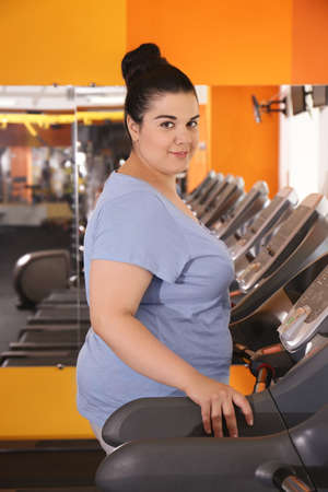 Overweight young woman training in gym