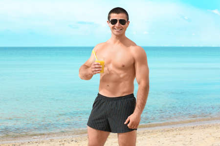 Handsome young man with drink on sea beach Stock Photo