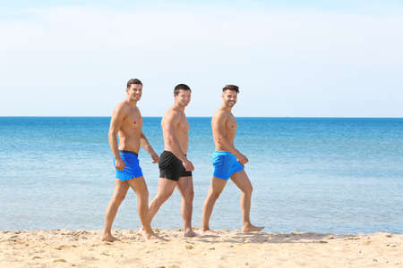Handsome young men walking on sea beach