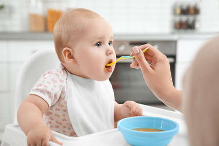 Mother feeding baby with spoon in kitchen