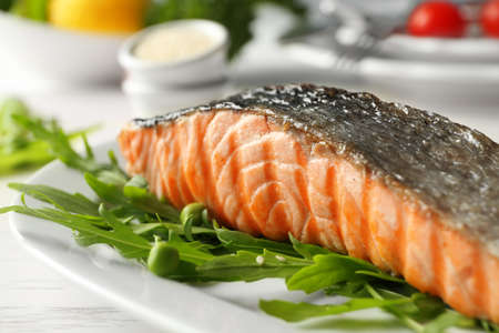 Plate with slice of delicious grilled salmon on table