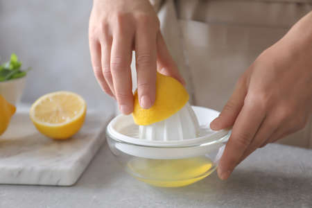 Man extracting lemon juice with plastic squeezer