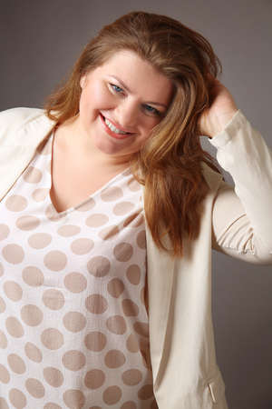Overweight stylish woman on grey background Stock Photo
