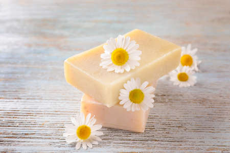 Two bars of soap and chamomile flowers on table