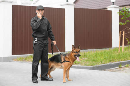 Guardia de seguridad con perro, al aire libre