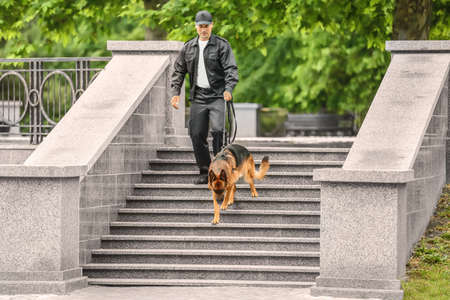 Security guard with dog on stairs Stock Photo