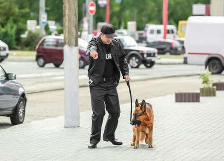 Guardia di sicurezza con cane, all'aperto Archivio Fotografico - 98385326