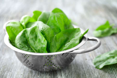 Colander with fresh spinach leaves on table
