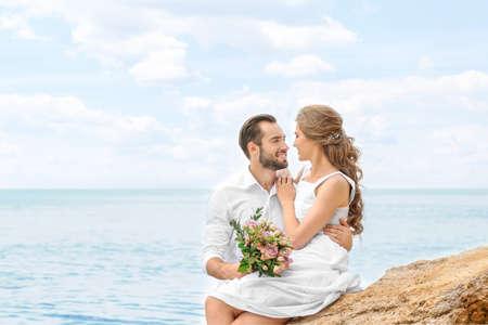 Happy newlywed couple sitting on rocky beach
