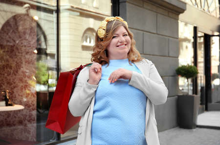 Beautiful overweight woman with shopping bags standing on street