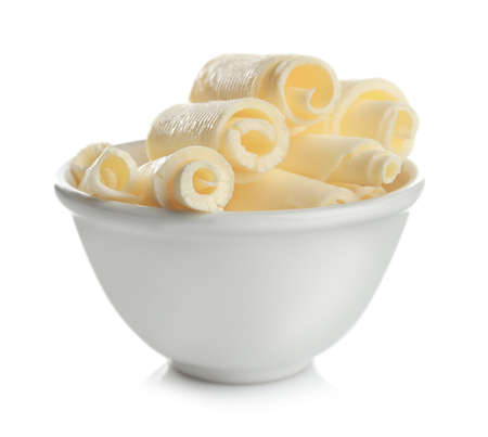 Bowl with delicious butter curls on white background