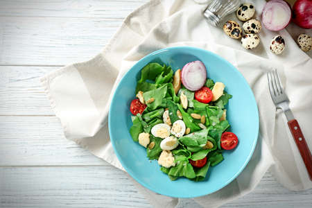 Salad with quail eggs and spinach in plate on table