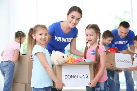 Happy volunteers with children holding donation boxes indoors