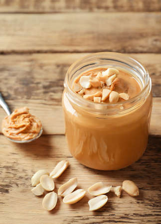 Jar with creamy peanut butter on table Banco de Imagens - 98225809