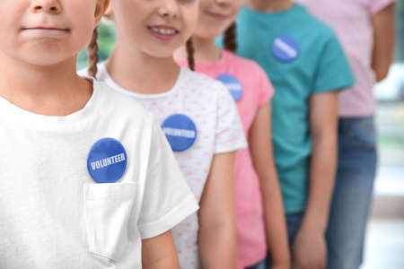 Children in shirts with volunteer buttons Stock Photo