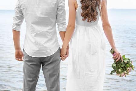 Newlywed couple standing on seashore