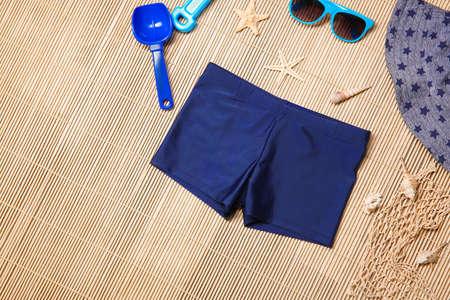 Set of boy's beach accessories on wicker background
