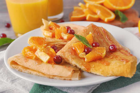 Delicious pancakes with orange and cranberry on plate