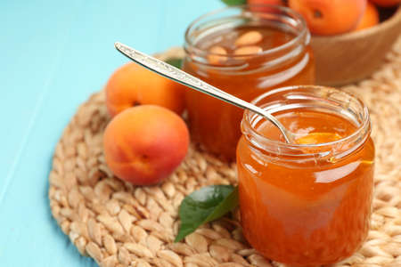 Apricot jam in jars with spoon and ripe juicy fruit on wicker mat